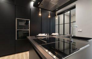 Muebles de cocina negros, placas de cocina y grifo