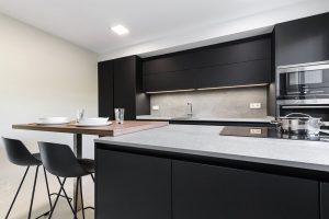 Cocina moderna negra con encimera porcelánica y barra de madera
