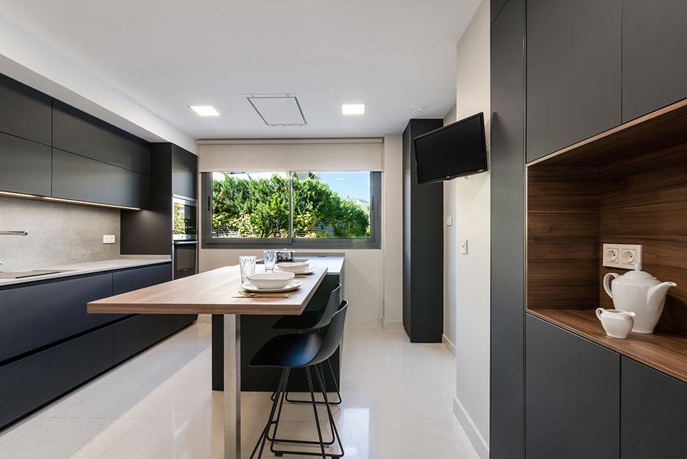 Cocina negra, encimera blanca y madera en trasera