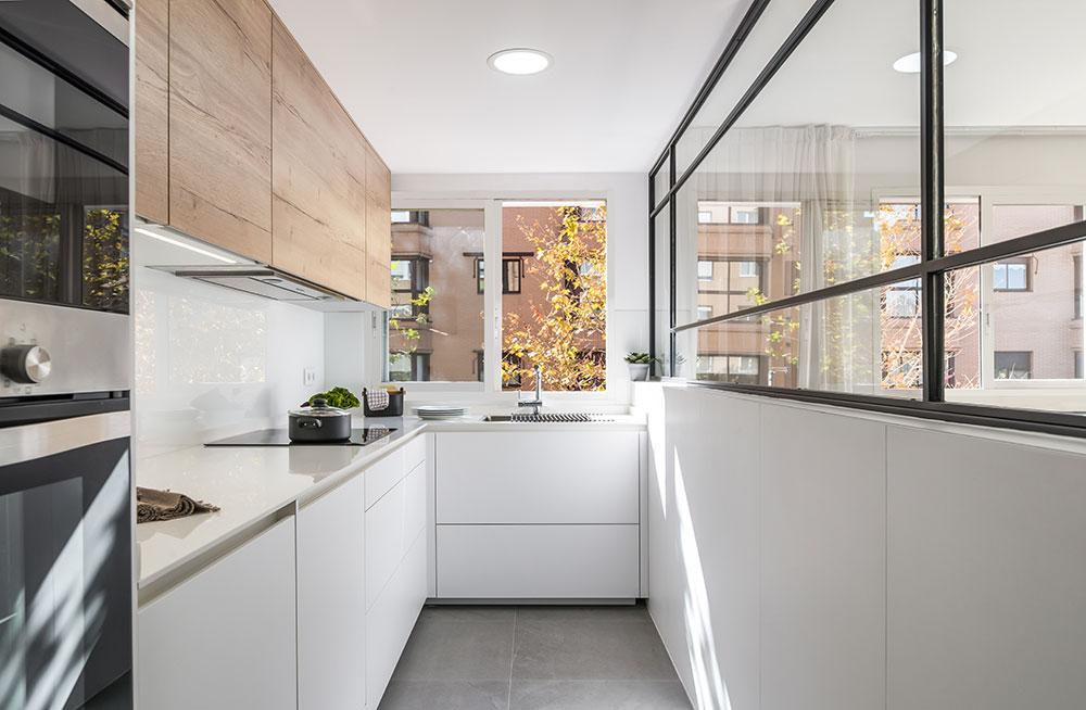 Cocina blanca abierta al salón con mampara de cristal